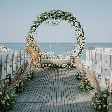 A circular arch sits in front of a port with white chairs and large tufts of pampas grass lining the walkway.