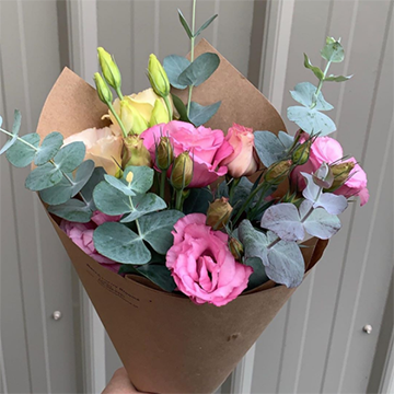 A paper-wrapped bouquet of hot pink lisianthus and eucalyptus greener is held in front of some white metal siding.