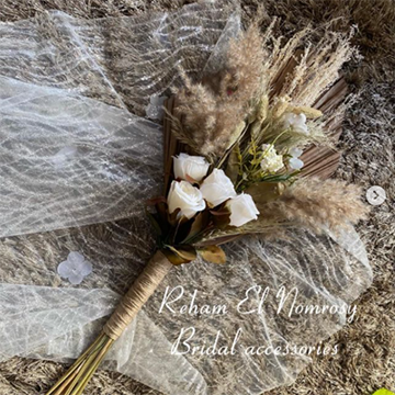 A simple pageant bouquet lays on a background of warm brown fur and white tulle. The bouquet is made of white roses, dried wheat grasses, and a tan ribbon handle.