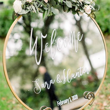 """""""Welcome Sara and Hunter February 1, 2020"""" is written in white calligraphy on a gold-framed round mirror with a small wreath of sage greenery and white flowers on top."""