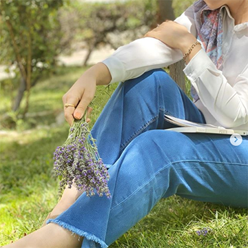 A woman in a white top and blue jeans sits on a grassy hill, holding a bundle of lavender flowers lazily over her legs.