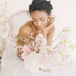 A beautiful bride with a pink and white bouquet featuring cherry blossoms, baby's breah, and a variety of twiggy flora.