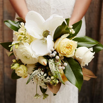 A bride holds her bouquet in front of her waist. The bouquet has a wide variety of white and off-white flowers, including magnolias, roses, and berries. The foliage is dark green leaves.