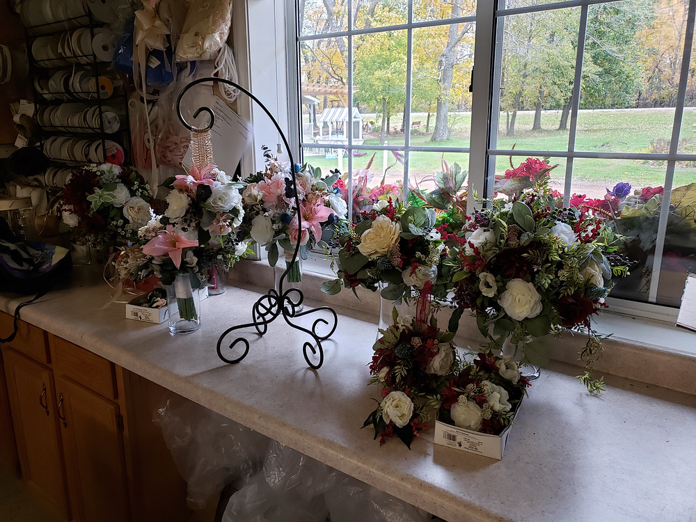 A variety of white, pink, and green wedding flowers on a white countertop.