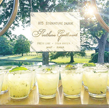 """A line of yellow drinks sits in front of a sign that says """"His signature drink - Southern Gentleman - Fresh Lime, Soda Water, Mint, Sugar"""" in an outdoor setting with the sun shining toward the camera."""