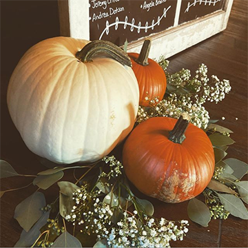 A large, white pumpkin sits next to two smaller, orange pumpkins that sit on some carefully-placed greenery and baby's breath.