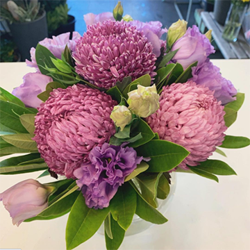 A purple bouquet of three giant blooms, some roses, and some carnations sits in a vase against a white background.