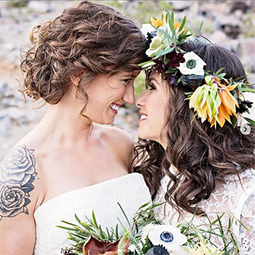 A woman in a white dress with short, curly brown hair smiles lovingly at another woman with large, white and yellow flowers in her hair, also wearing a white dress, and holding a matching bouquet.