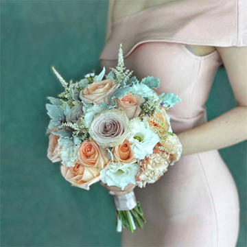 A woman in a light pink dress holds a bouquet with white, light peach, and light blue flowers in front of a teal background.