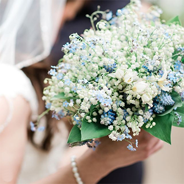 A bride (out of focus) holds a bright white and light blue bouquet of forget-me-nots and lily of the valley.