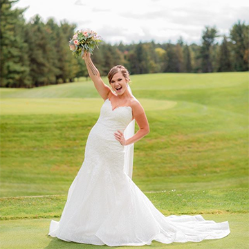 A bride stands in an open golf course with pine trees in the background, holding her bouquet of pink flowers and greenery up in the air with a wide smile and her other hand on her hip.