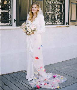 A bride stands in front of a white wall with colonial iron windows. She holds a large round bouquet and has pink, purple, and blue flowers interspersed in her veil.