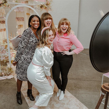 Four women pose in front of a camera with smiles. The woman closest to the camera is blonde and wears a white brides' robe while the rest wear fun pink, white, and black outfits.
