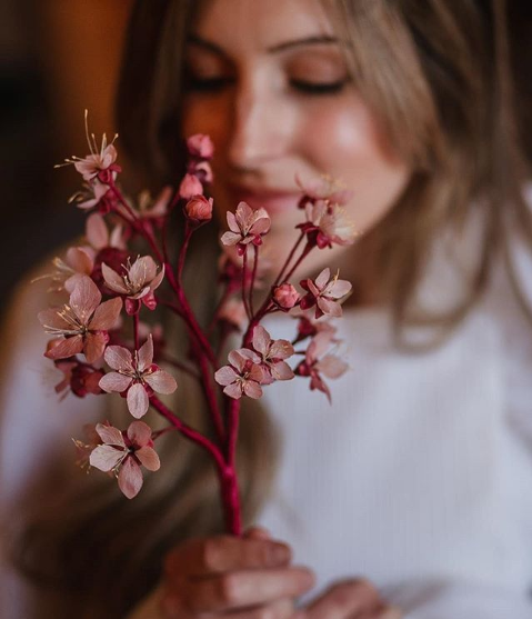 A woman holding a deep pink sprig of cherry blossoms close to the camera.