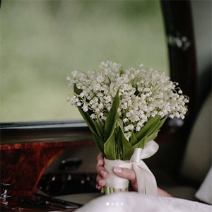 A woman holds a hand-tied bouquet of lily of the valley while riding in a car.