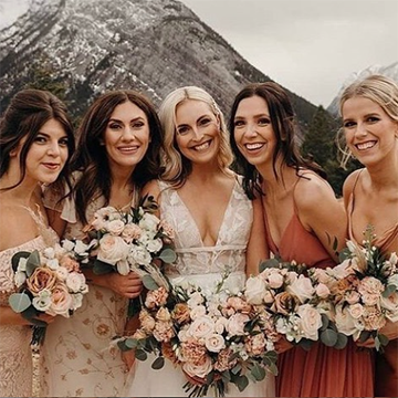 four bridesmaids surround a smiling bride while they all hold bouquets of light peaches, browns, whites, and dark sage greenery while posing in front of a mountain.