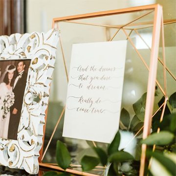 A frame sits with a prayer in it, decorated with greenery and a vintage wedding photo in another frame overlapping in front of it.