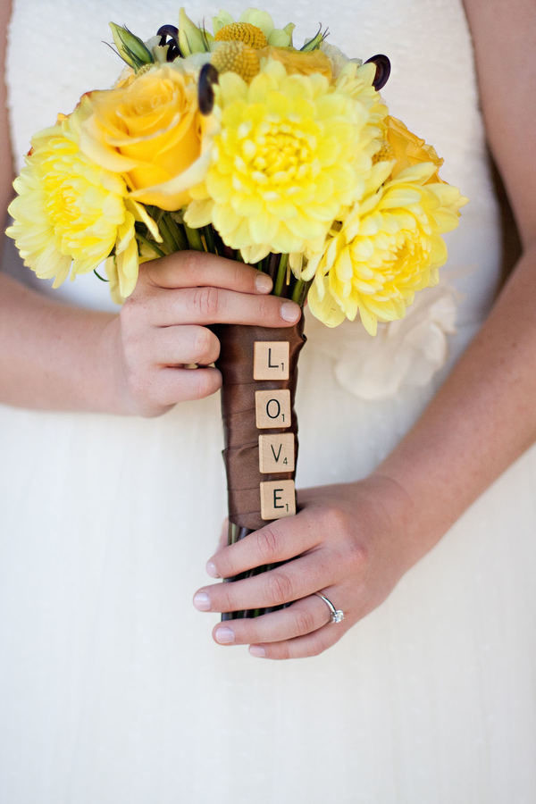 """A bride holds a small bouquet of yellow flowers with a brown ribbon handle. Down the side of the handle are four scrabble tiles that read top to bottom: """"Love."""""""