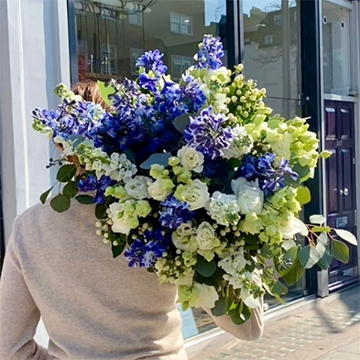 A person in abeige sweater holds a large, messy bouquet of yellow and blue flowers with sage greenery over their shoulder.