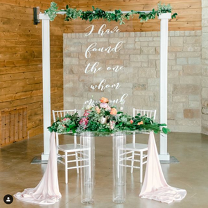 """An altar of two white pillars with an elegant sign behind that says, """"I have fount the one whom [illegible]"""" and a table in front of it with a gorgeous flower arrangement of white, pink, and peach colored flowers and messy greenery."""
