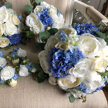 A large bridal bouquet and its matching smaller bridesmaids bouquets and boutonnieres sit on a cream-colored chair. The bouquets have large, white peonies and roses and tightly-packed dark blue forget-me-nots with small bits of greenery. They are round bouquets.