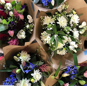A cluster of bouquets wrapped in brown tissue paper viewed from above. The bouquets have white, light blue, pink, and purple flowers and various greeneries.