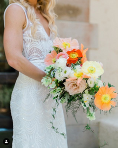 A bride holds a bouquet of light peach, white, orange, pink, and red poppies with various greenery in front of her white dress.