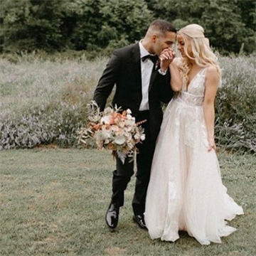 A groom kisses his bride's hand sweetly while holding her bouquet at his side.