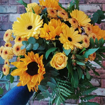 A bouquet of yellow sunflowers, garden daisies, roses, and marigolds is held against a red brick wall.