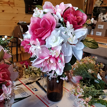 A bouquet of white and pink large blooms, pearls, small stargazer lilies, and cattails hanging from the bottom, sat on a work table.