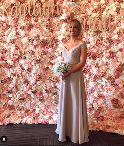 """A bride holds her white bouquet while standing in front of a wall of pink flowers that has two signs that read, """"Kayleigh and Matt."""""""