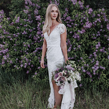 A bride with blonde hair holds a bouquet of purple and white flowers at her side while standing in front of a wall of purple lilacs.