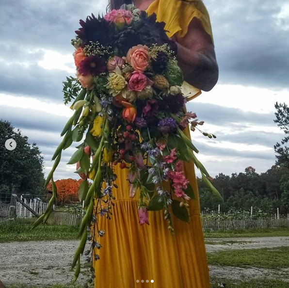A woman in a yellow dress holds a messy cascade bouquet full of greenery with large leaves and pink, peach, purple, dark red, and small white flowers.