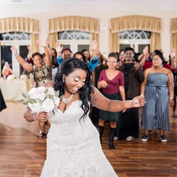 A black bride wearing shiny white eye shadow and a sleeveless wedding gown with blingy silver jewelry is dancing on a wooden dance floor with her friends and family behind her. She holds a white bouquet close to her face in a natural fashion.
