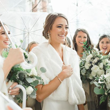 A bride is surrounded by bridesmaids smiling and holding white-handled, clear umbrellas and cascade style bouquets with white roses and messy greenery while the bride holds a fluffy shawl around her shoudlers.