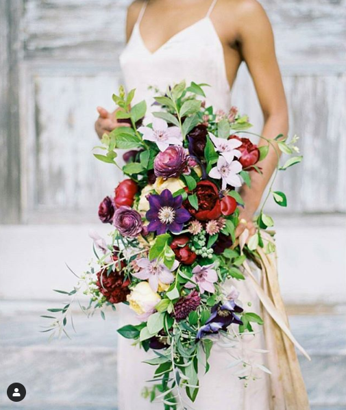 A bride holds a large, messy bouquet of purple, red, and white flowers and leafy greenery.