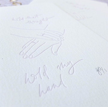 "A drawing of two hands holding each other and the words, ""hold my hand"" are embossed into a sheet of textured white paper."