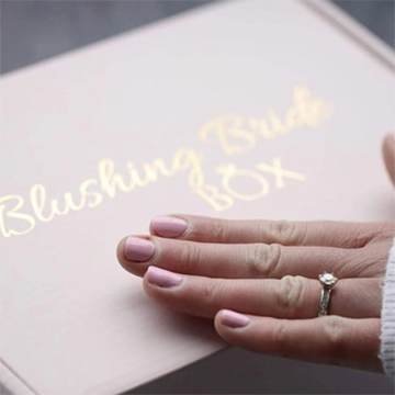 """A caucasian woman with pink fingernails and a small diamond ring on her finger brushes her hand across the top of a light pink box with gold lettering that says, """"Blushing Bride Box""""."""