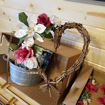 A woven stick wreath in the shape of a heart with large white and red blooms and small white blooms decorating one edge.