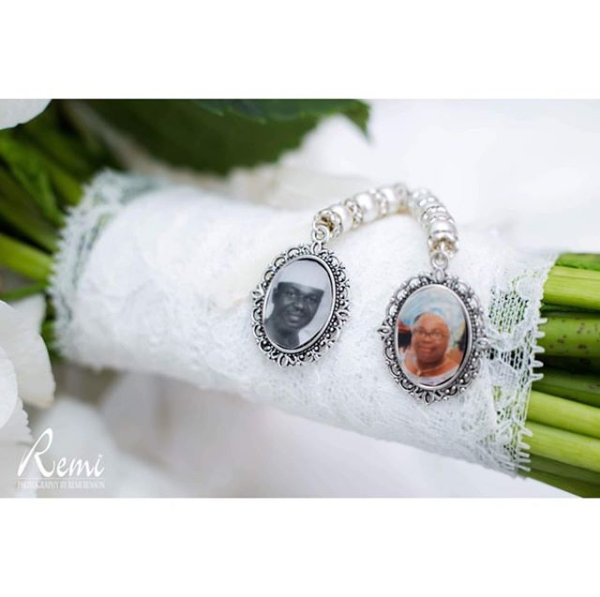 A green bouquet handle wrapped in white lace with two silver charms holding pictures of loved ones passed.