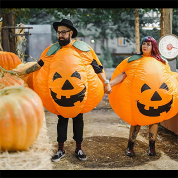 A man and a woman walk through a pumpkin patch while wearing round, inflatable orange jack-o-lantern costumes and holding hands.