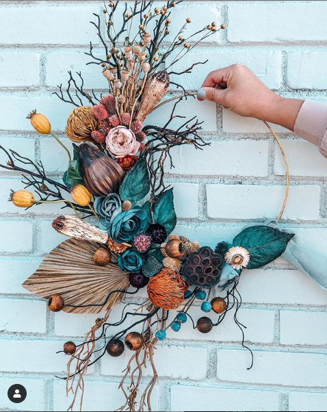 A hoop bouquet with teal, nontraditional flowers such as seed pods and large leaves.