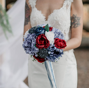 A bride in a lacy short-sleeved dress with a sweetheart neckline holds a bouquet with blue ribbons hanging of the handle, red and white rose-like flowers, and blue hydrangea and succulent-esque flowers in front of her belly.