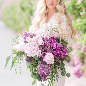 A bride with long, flowing blonde hair holds a purple and white cascading bouquet with messy greenery while in the sunshine.