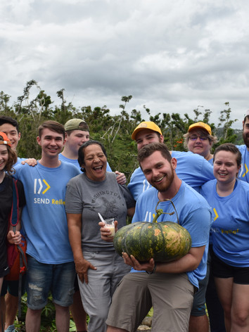 The team poses with a local watermelon