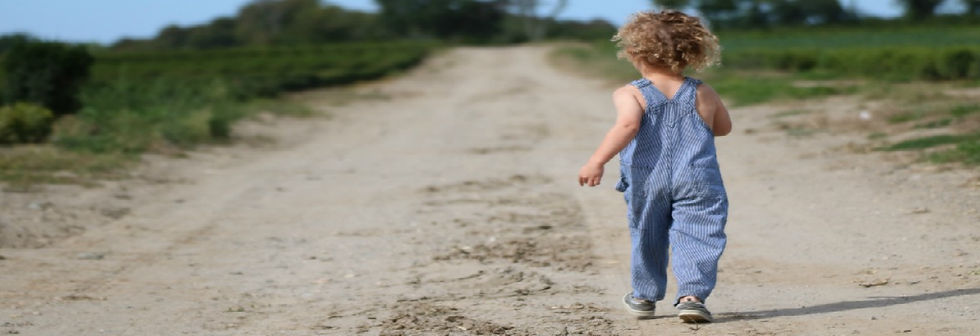 Child walking on a dirt road.