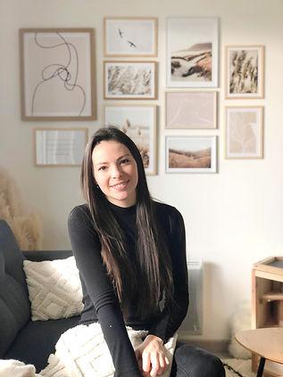 Portrait de Léa Blandel Décoration dans un salon. A l'arrière un mur de cadre dans des tons neutres et naturels. Une décoration bohème/ scandinave.