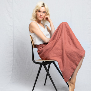 A blonde woman sitting on a wooden chair wearing a black and white striped tank top and a salmon colored maxi skirt.