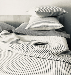 A stack of gray and white striped linen pillows on a bed.