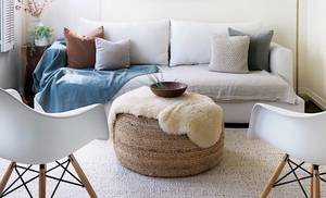 A blue linen throw blanket sits on a white couch with four throw pillows. In front of the couch is a seagrass ottoman with a fur blanket thrown over it and a wooden bowl on top. There are two white chairs facing the white couch.